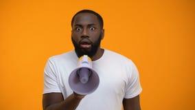Hombre negro asustado que grita en el megáfono, información de extensión, conciencia almacen de video