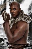 Hombre negro atractivo con la serpiente del constrictor de boa imagenes de archivo