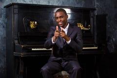 Hombre negro cerca del piano Fotografía de archivo libre de regalías
