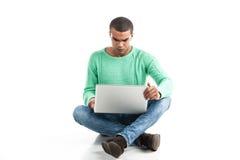 Hombre negro con el ordenador portátil sobre el fondo blanco Imagen de archivo libre de regalías