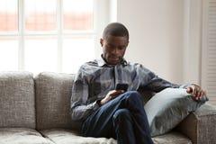 Hombre negro con el teléfono que se sienta en el sofá en casa imagen de archivo libre de regalías