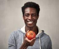 Hombre negro con el tomate Imagen de archivo libre de regalías