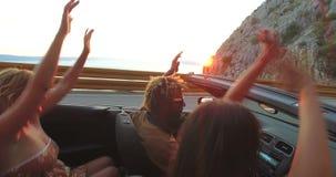 Hombre negro con los dreadlocks que va de fiesta con los amigos mientras que conduce en convertible almacen de video