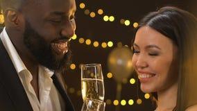 Hombre negro confiado que liga con champán asiático de la señora, de la charla y de la consumición almacen de video