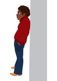 Hombre negro de la historieta en el suéter rojo que se coloca cerca de la pared Fotos de archivo