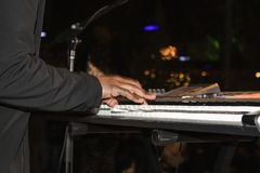 Hombre negro en el traje negro que juega el teclado en la noche con el fondo del bokeh - falta de definición del movimiento foto de archivo