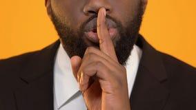 Hombre negro en el traje que muestra la muestra del silencio, evasión fiscal ilegal, secreto corporativo metrajes