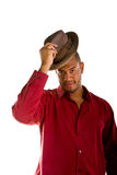 Hombre negro en la camisa roja que inclina un sombrero de Brown Fotos de archivo