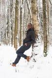 Hombre negro en la nieve contra un árbol Imagen de archivo libre de regalías