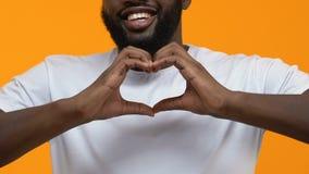 Hombre negro feliz en la camiseta blanca que muestra las manos de la muestra del corazón, gesto de la caridad, amor almacen de metraje de vídeo