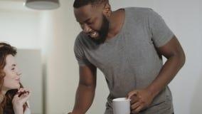 Hombre negro feliz que trae tazas de té a la mujer bastante blanca en la cocina moderna almacen de video