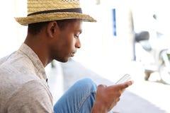 Hombre negro fresco que mira el teléfono móvil Fotografía de archivo libre de regalías