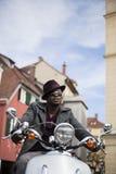Hombre negro fresco que monta una vespa Imagen de archivo