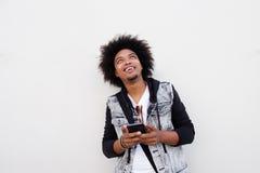 Hombre negro fresco que sostiene el teléfono móvil y que mira para arriba Fotografía de archivo libre de regalías