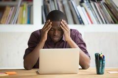 Hombre negro frustrado que siente presionado después del fall que se sienta con l Imágenes de archivo libres de regalías