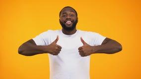 Hombre negro hermoso que sonríe con confianza, mostrando los pulgares para arriba en fondo amarillo almacen de metraje de vídeo