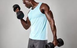Hombre negro joven apto que ejercita con pesas de gimnasia fotos de archivo libres de regalías