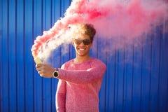 Hombre negro joven del inconformista que sonríe y que sostiene un humo rosado colorido Fotografía de archivo