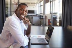 Hombre negro joven en oficina con el ordenador portátil que sonríe a la cámara Foto de archivo libre de regalías