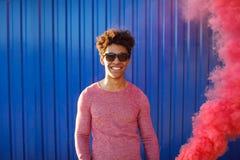 Hombre negro joven en un suéter que se coloca al lado de la pared azul Foto de archivo