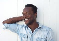 Hombre negro joven feliz que sonríe contra el fondo blanco al aire libre Imagen de archivo libre de regalías