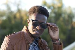 Hombre negro joven hermoso en gafas de sol y una chaqueta de cuero en a Fotografía de archivo