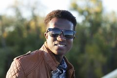 Hombre negro joven hermoso en gafas de sol y una chaqueta de cuero en a Fotos de archivo