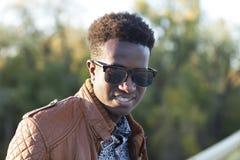 Hombre negro joven hermoso en gafas de sol y una chaqueta de cuero en a Imagen de archivo libre de regalías