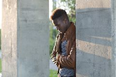 Hombre negro joven hermoso que se inclina en una pared que mira abajo Imágenes de archivo libres de regalías