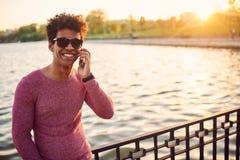 Hombre negro joven que habla en el teléfono y la sonrisa Imagen de archivo libre de regalías