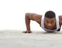 Hombre negro joven que hace pectorales al aire libre Foto de archivo libre de regalías