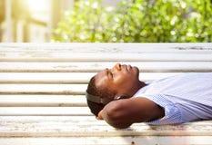Hombre negro joven que miente en un banco de parque con los auriculares Fotografía de archivo