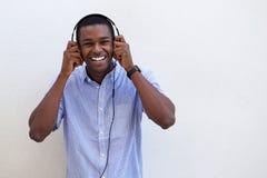 Hombre negro joven que ríe con los auriculares Foto de archivo