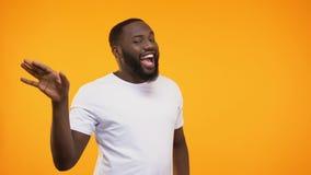 Hombre negro joven que realiza la danza feliz, mostrando gestos aliviados en la cámara almacen de metraje de vídeo