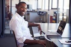 Hombre negro joven que se sienta en el escritorio en la oficina que sonríe a la cámara fotos de archivo
