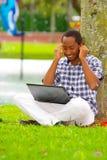 Hombre negro joven que se sienta en hierba verde y que trabaja en su ordenador y música que escucha con su presentación de los au Imagen de archivo libre de regalías