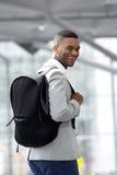 Hombre negro joven que sonríe con el bolso en el aeropuerto Foto de archivo libre de regalías