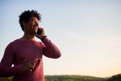 Hombre negro joven que sonríe y que habla en el teléfono móvil afuera Fotos de archivo libres de regalías
