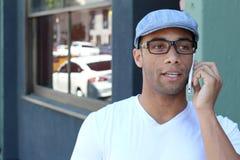 Hombre negro joven que sonríe y que habla en el teléfono móvil afuera con el espacio de la copia Fotografía de archivo