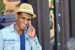 Hombre negro joven que sonríe y que habla en el teléfono móvil afuera con el espacio de la copia Imagen de archivo libre de regalías