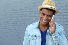 Hombre negro joven que sonríe y que habla en el teléfono móvil afuera con el espacio de la copia a la izquierda Foto de archivo libre de regalías
