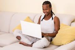 Hombre negro joven que usa el ordenador portátil en el sofá Fotos de archivo