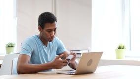 Hombre negro joven que usa Smartphone, en línea hojeando almacen de metraje de vídeo