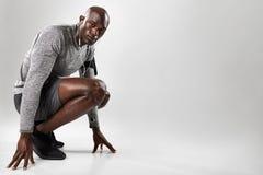 Hombre negro joven sano que se arrodilla en fondo gris foto de archivo