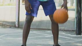 Hombre negro juguetón que hace trucos con la bola, jugando a baloncesto, forma de vida activa metrajes