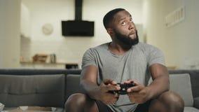 Hombre negro juguetón que juega al videojuego en la cocina Hombre del trastorno que lanza hacia fuera la palanca de mando almacen de metraje de vídeo