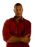 Hombre negro ocasional en los brazos rojos de la camisa cruzados Imagen de archivo