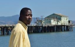 Hombre negro por el agua enojada Imagenes de archivo