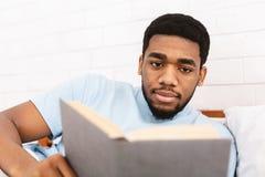 Hombre negro que estudia la literatura del negocio en cama foto de archivo libre de regalías