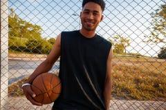 Hombre negro que juega al baloncesto, bola de la calle, hombre que juega, competencias de deporte, afro, retrato al aire libre Foto de archivo libre de regalías
